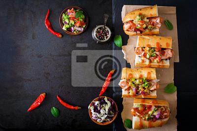 Hot dog - kanapka z meksykańską salsą na ciemnym tle. Widok z góry