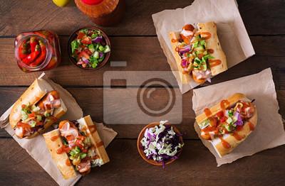 Hot dog - kanapka z meksykańską salsą na tle drewnianych. Widok z góry