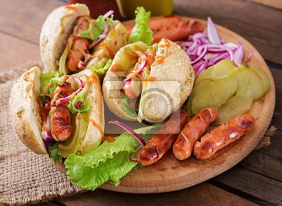 Hot dog - kanapka z ogórków, czerwona cebula i sałaty na tle drewnianych. Widok z góry