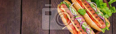 Hot dog with  sausage, cucumber, tomato and lettuce on dark wooden background. Summer hotdog. Top view. Banner