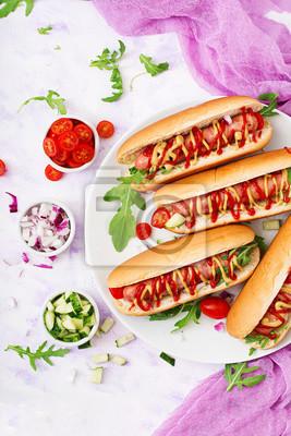 Hot dog z kiełbasą. boczek, ogórek, pomidor i czerwona cebula na białej płytce. Widok z góry. Płaskie leże.