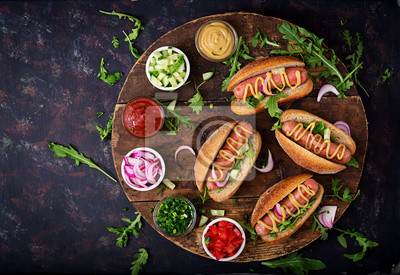 Hot dog z ogórkiem, pomidorem i czerwoną cebulką na drewnianym tle. Widok z góry. Płaskie leże