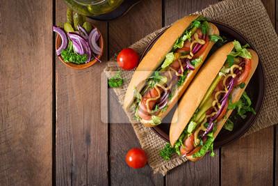 Hot dog z ogórkiem, pomidorem i sałatą na drewnianym tle