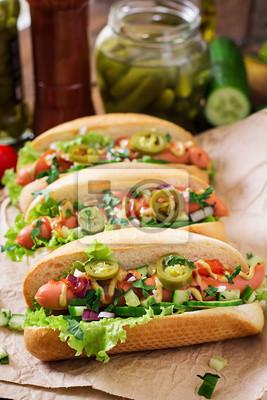 Hot dog z papryką jalapeno, pomidorów, ogórków i sałaty na drewnianym tle