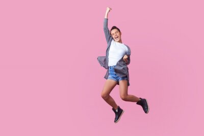Plakat I did it! Energetic teen girl with bun hairstyle in casual clothes jumping with closed eyes and raised fists, crazy about winning, screaming and dancing with happiness in the air, celebrating success