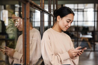 Plakat Image of young asian woman holding cellphone while working in office
