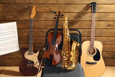 Plakat Instrumenty muzyczne na krześle i notatki posiadacza przed drewnianym tle