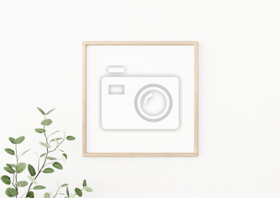 Plakat Interior poster mockup with square wooden frame on empty white wall decorated with plant branch with green leaves. 3D rendering, illustration.