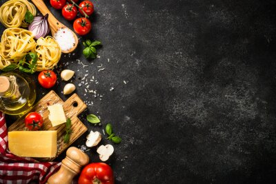 Plakat Italian food background black table. Raw Pasta, fresh tomatoes, olive oil, parmesan, spices and basil. Top view with copy space.