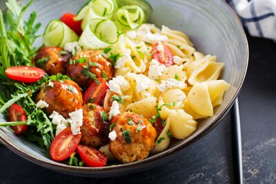 Italian pasta. Conchiglie with meatballs, feta cheese and salad on dark background. Dinner.  Slow food concept