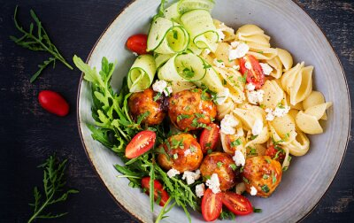 Italian pasta. Conchiglie with meatballs, feta cheese and salad on dark background. Dinner. Top view, overhead. Slow food concept