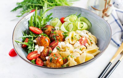 Italian pasta. Conchiglie with meatballs, feta cheese and salad on light background. Dinner. Slow food concept
