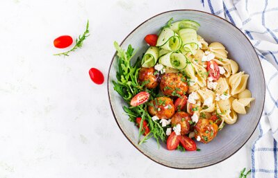 Italian pasta. Conchiglie with meatballs, feta cheese and salad on light background. Dinner. Top view, overhead. Slow food concept