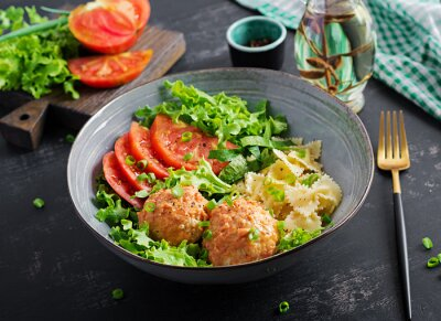 Italian pasta. Farfalle with meatballs and salad on dark background. Dinner. Slow food concept