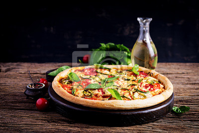 Italian pizza with chicken, salami, zucchini, tomatoes and herbs on vintage wooden background.  Italian cuisine