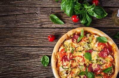 Italian pizza with chicken, salami, zucchini, tomatoes and herbs on vintage wooden background. Top view. Italian cuisine