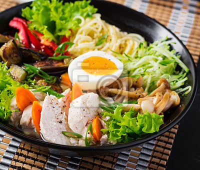 Japanese ramen soup with chicken, egg, shimeji mushrooms and eggplants on dark wooden background. Chanko nabe, sumo soup.