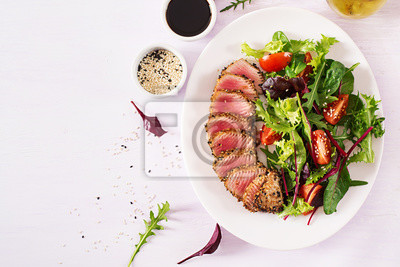 Japanese traditional salad with pieces of medium-rare grilled Ahi tuna and sesame with fresh vegetable salad on a plate. Authentic Japanese food. Top view. Copy space.
