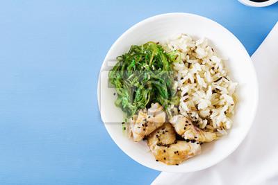 Japońskie jedzenie. Miska ryżu, gotowana biała ryba i wakame chuka lub sałatka z wodorostów. Widok z góry. Leżał płasko