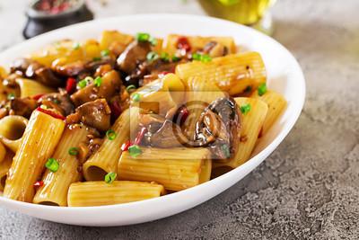 Jarski makaron rigatoni z pieczarkami i chili pieprzami w białym pucharze na popielatym stole. Wegańskie jedzenie.