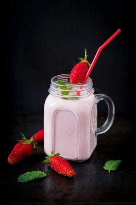 Jogurt truskawkowi smoothies w słoju na czarnym tle
