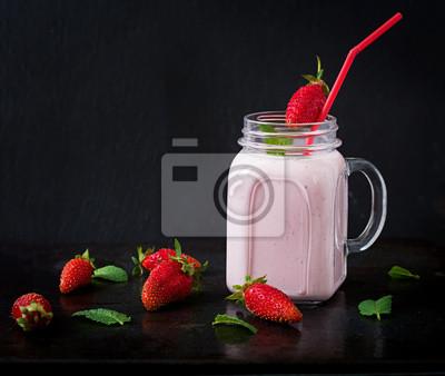 Jogurt truskawkowy smoothies w słoiku na czarnym tle
