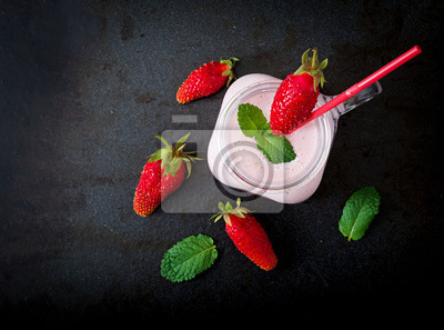 Jogurt truskawkowy smoothies w słoiku na czarnym tle. Płaskie leże. Widok z góry