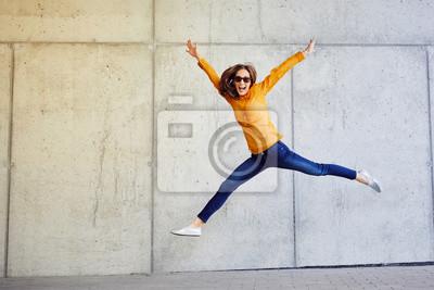 Plakat Joyful młoda dama skoków i podnoszenie broni przed ścianą na zewnątrz