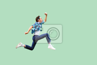 Plakat Jump to the success. Full length profile side view of active young man in casual blue checkered shirt and headband running very fast or jumping. indoor studio shot, isolated on green background.