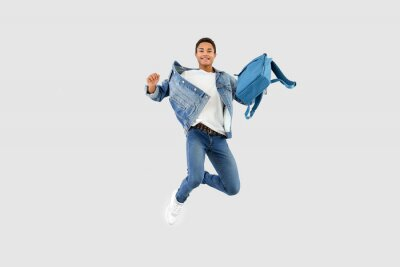 Plakat Jumping African-American teenager boy with backpack on white background