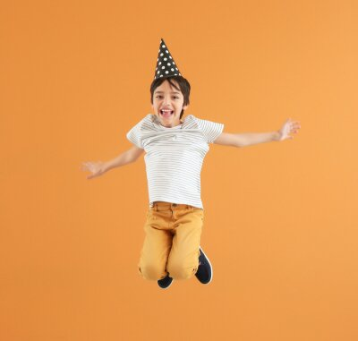 Plakat Jumping little boy with party hat on color background