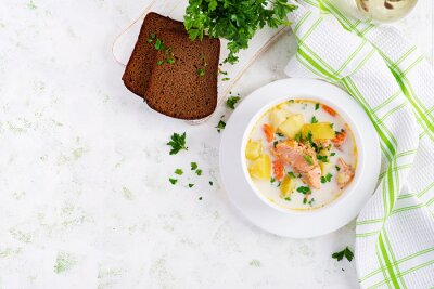 Kalakeitto. Creamy soup with salmon, potatoes, onions and carrots and  in a bowl. Finnish/ karelian cuisine. Lohikeitto. Top view, overhead, flat lay