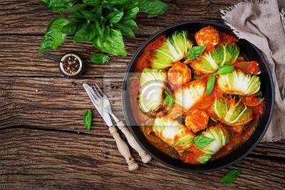 Kapusta rolki faszerowane ryżem z filetem z kurczaka w sosie pomidorowym na drewniane tła. Smaczne jedzenie. Widok z góry. Płaskie leżało