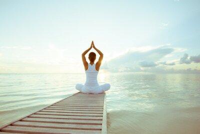 Plakat Kaukaski kobieta uprawiania jogi na brzegu morza