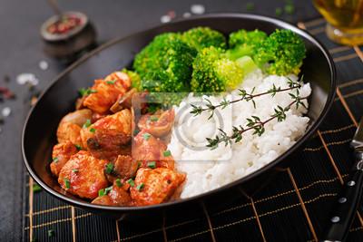 Kawałki fileta z kurczaka z grzybami duszone w sosie pomidorowym z gotowanymi brokułami i ryżem. Odpowiednie odżywianie. Zdrowy tryb życia. Dietetyczne menu.