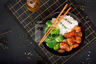 Kawałki fileta z kurczaka z grzybami duszone w sosie pomidorowym z gotowanymi brokułami i ryżem. Odpowiednie odżywianie. Zdrowy tryb życia. Dietetyczne menu. Widok z góry