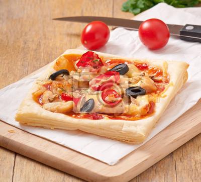 kawałki pizzy z kurczakiem i pomidorami