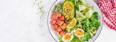 Ketogenic diet breakfast. Salt salmon salad with greens, cucumbers, eggs and avocado. Keto/paleo lunch. Top view, banner