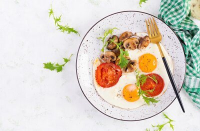 Ketogenic food. Fried egg, mushrooms and sliced tomatoes. Keto, paleo breakfast. Top view, overhead, copy space