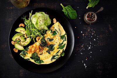 Ketogenic, paleo diet breakfast. Omelette with spinach and avocado, cucumber. Top view, copy space