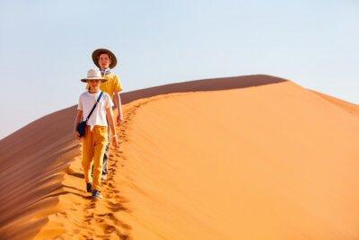 Plakat Kids climbing up red sand dune