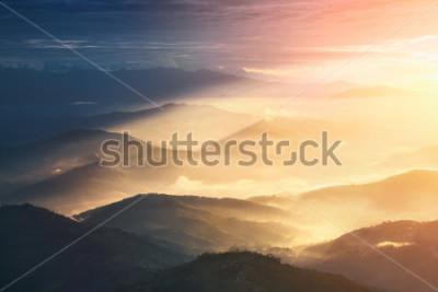 Plakat Kiedy noc staje się dniem. Piękni wzgórza jaskrawy zaświecający podczas wschodu słońca.