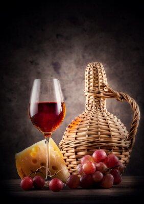 Plakat Kieliszek czerwonego wina z karafki i winogron