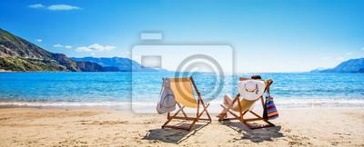 Plakat Kobieta cieszy się sunbathing przy plażą