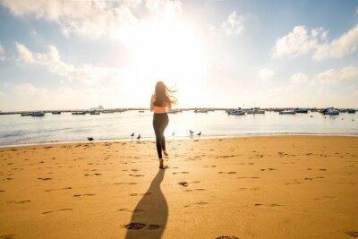 Plakat Kobieta działa na piaszczystej plaży
