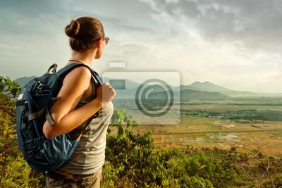 Kobieta podróżników z plecak stojących korzystających z widokiem na góry o zachodzie słońca