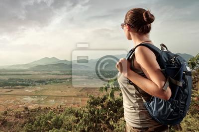 Kobieta podróżująca z plecakiem stałego korzystających z górskich widoku podczas zachodu słońca.