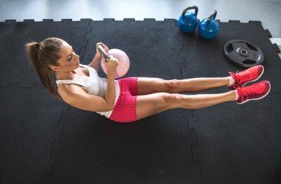 Plakat Kobieta pracująca na jej brzucha z Kettlebell