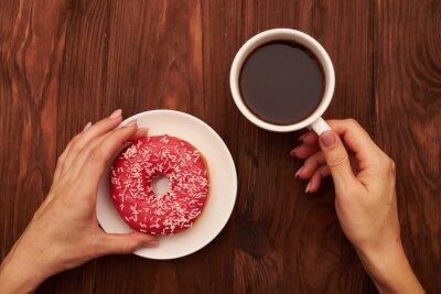 Plakat Kobieta strony gospodarstwa filiżanka kawy i różowego pączka
