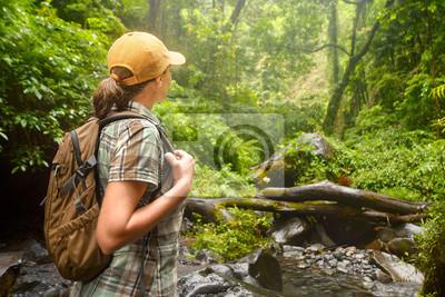Plakat Kobieta turystą z plecak stojących korzystających z dżungli.